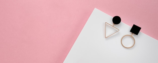 Panoramic shot of geometric modern earrings on white and pink background with copy space