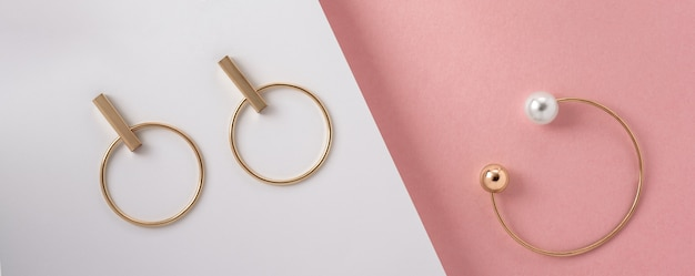 Panoramic shot of golden bracelet and earrings flat lay on pink and white paper