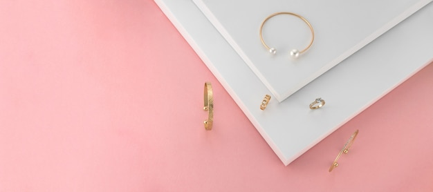 Panoramic shot of golden jewelries on pink and white paper background