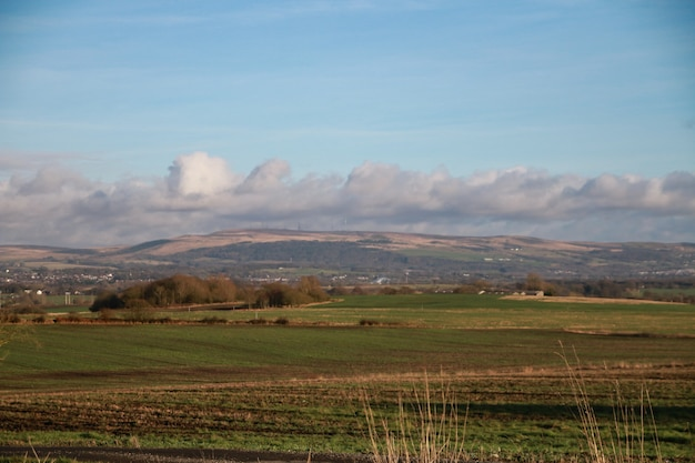 Panoramic shot of green fields and hills under a cloudy blue sky