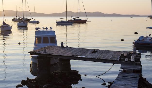 Foto panoramica di un porto con barche a vela e un vecchio molo