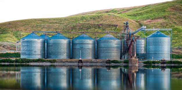 Panoramic shot of industrial buildings on the shore of the lake reflected in the water