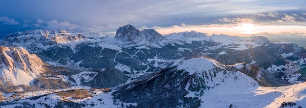 Panoramic shot of mountains covered in snow at sunset