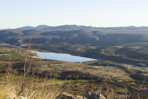 曇り空の下でなだらかな丘の間の湖のパノラマ写真