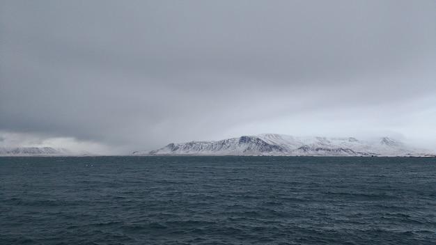 흐린 날에 눈이 덮여 산 해안의 파노라마 샷