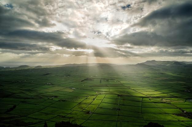 雲の切れ間から太陽の光が差し込む農地のパノラマ写真