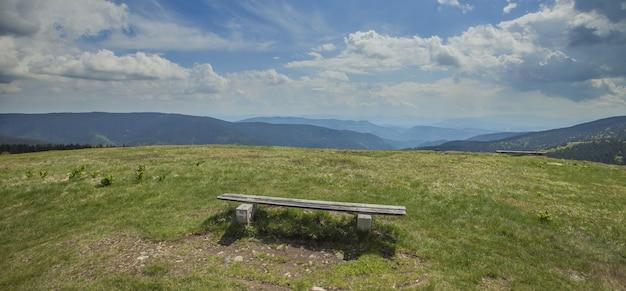 スロベニアのリブニカ湖の近くのフィールドに空の木製ベンチのパノラマ撮影