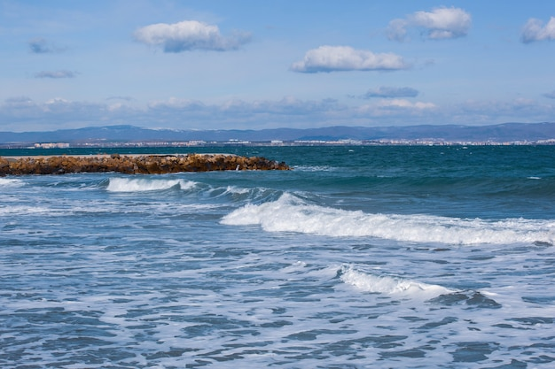 曇り空の下で波打つ石とドックの海のパノラマ撮影