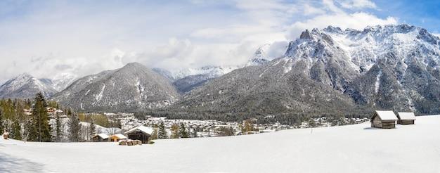 雪に覆われた美しい山々やコテージのパノラマ写真