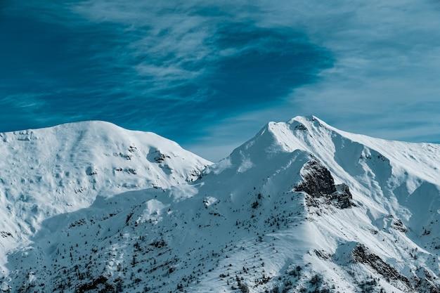Панорамный снимок заснеженных горных вершин под пасмурным голубым небом