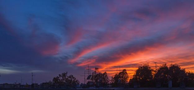 古い建物のアンテナシルエットと新しいザグレブの夕日のパノラマ写真