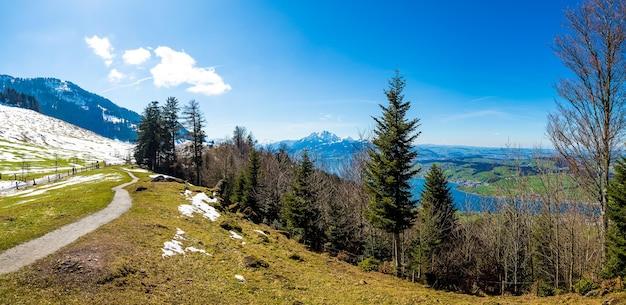 スイスの青い空の下の美しい山々のパノラマ写真