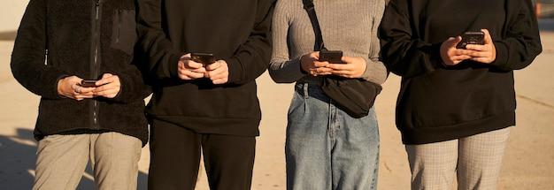 스마트 폰을 사용하는 친구 그룹의 손의 파노라마 샷.