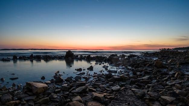 日の出の間に澄んだ空と岩の海岸のパノラマ写真