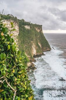 曇り空の下でインドネシアのバリ島のウルワツの崖のパノラマ写真