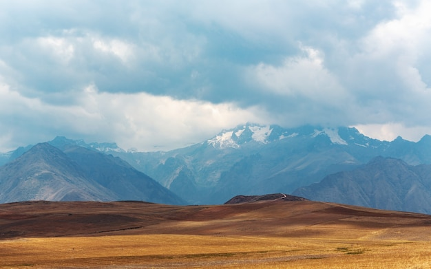 Panoramic shot of a plain with mountains touching the sky