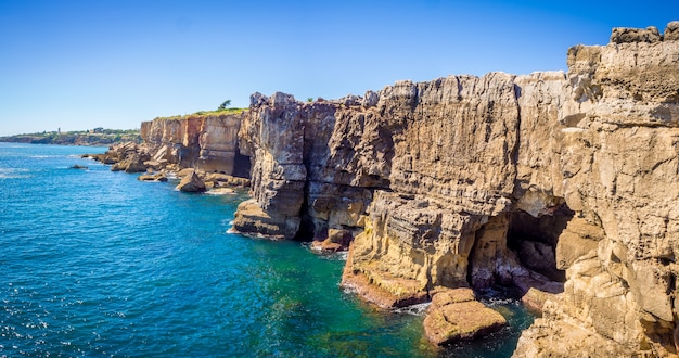 Panoramic shot of the rocks beside the ocean in cascais, portugal