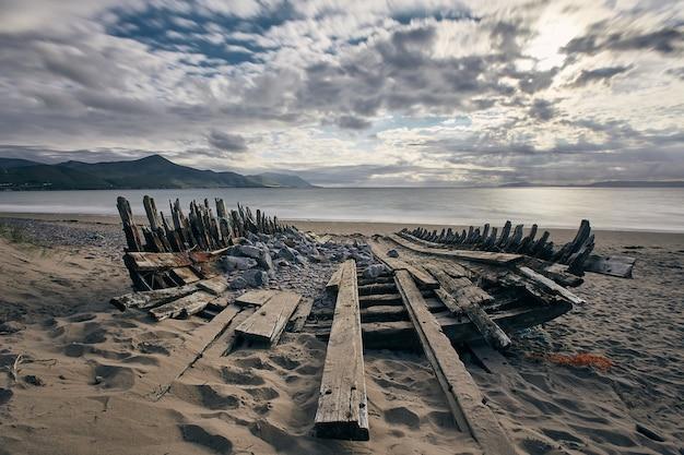 Ripresa panoramica di una barca naufragata sulla riva di rossbeigh strand