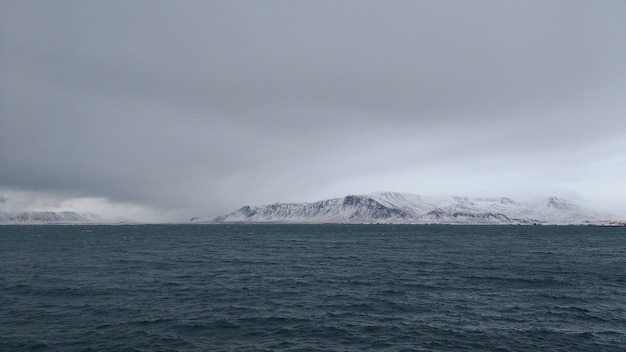 Panoramic shot of a snow covered mountain coast on a cloudy day