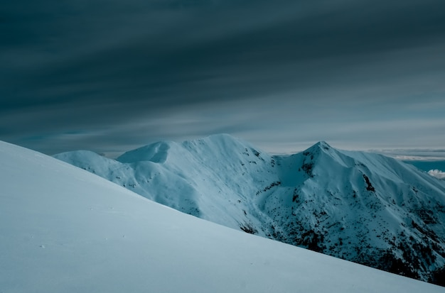 Panoramic shot of snow covered mountain peaks under cloudy skies