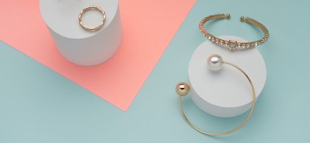 Panoramic shot of two golden bracelets and ring on pink and blue wall
