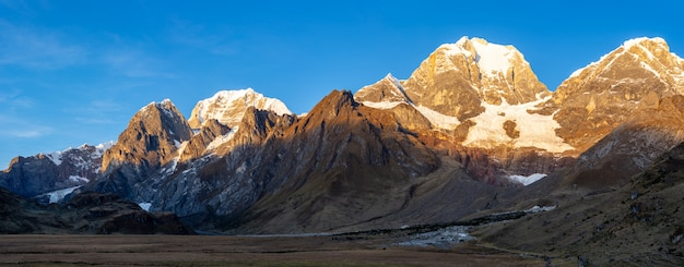 Panoramic shot of a valley at the base cordillera huyahuash, peru with its peak covered in snow.