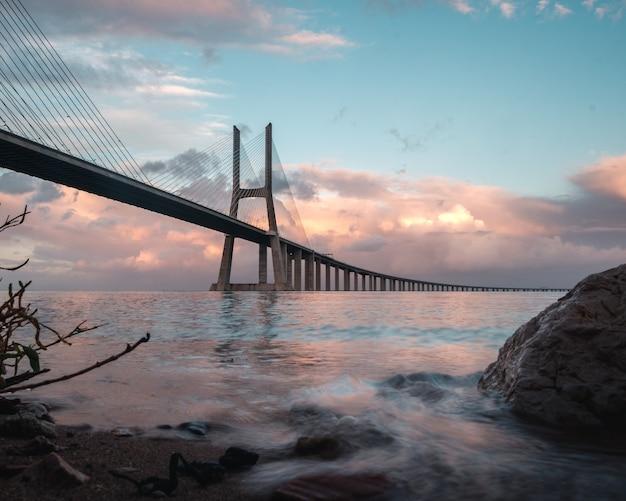 Panoramic shot of the vasco da gama bridge located in sacavém, portugal under the beautiful pink sky