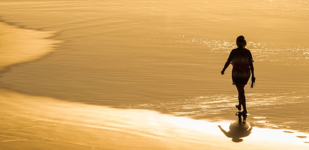 Panoramic shot of a woman walking on the beach at golden hour in brazil