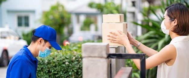 顔マスクの顧客とパノラマの側面図アジアの女性は非接触でショッピングパッケージを取る