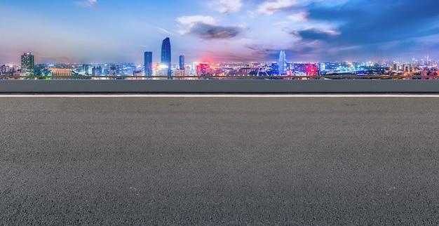 Панорамный горизонт и пустая асфальтированная дорога с современными зданиями