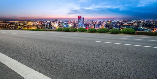パノラマのスカイラインとモダンな建物のある空のアスファルト道路 Premium写真