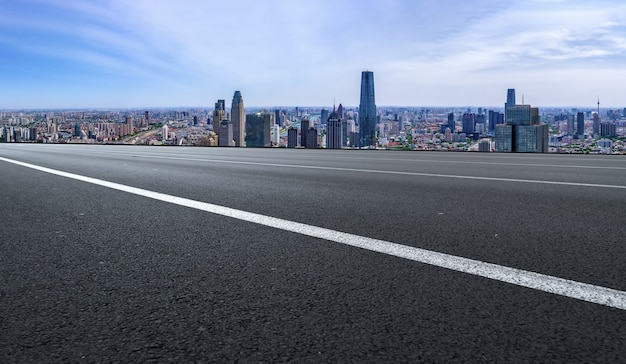 パノラマのスカイラインとモダンな建物のある空のアスファルト道路