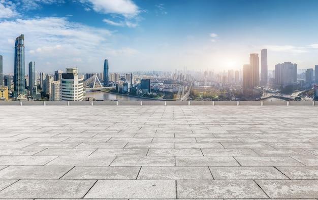 パノラマのスカイラインとモダンな建物の空の正方形の床タイル Premium写真