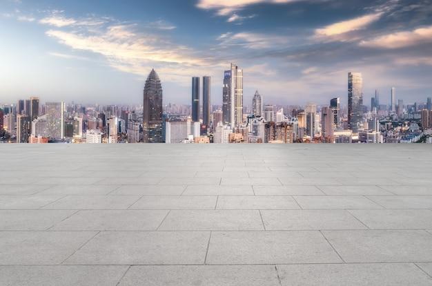 Панорамный горизонт и пустая квадратная напольная плитка с современными зданиями