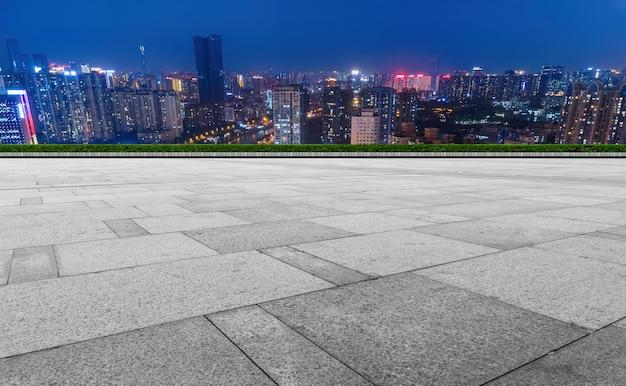 パノラマのスカイラインとモダンな建物の空の正方形の床タイル