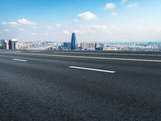 Panoramic skyline and empty asphalt road with modern buildings