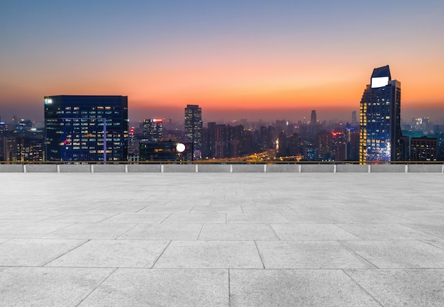 Panoramic skyline and empty square floor tiles with modern buildings