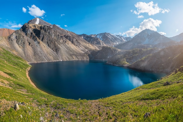 山々を背景に山の湖を丸くする春のパノラマビュー。ハイキング中に紺碧の大きな池がある山々にあるゴージャスな青い山の湖。