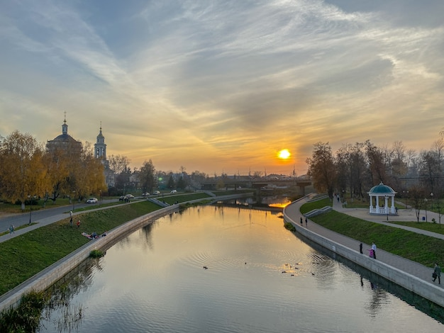 Panoramic sunset city view of the river, promenade, old churches against the sky with clouds