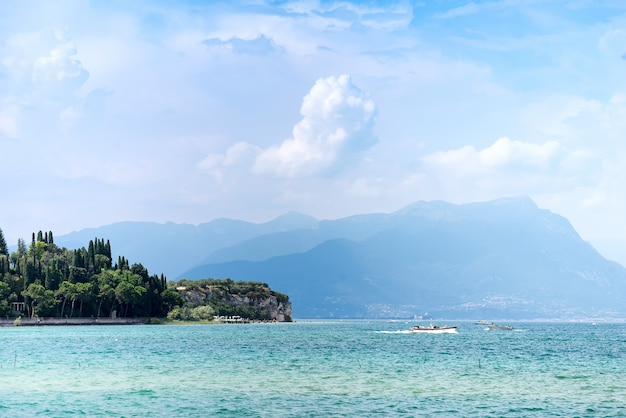 Panoramic view against bright sun rays above the rocks on beautiful garda lake shore in riva del garda city in lombardy