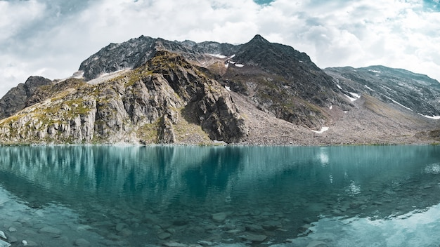 Panoramic view of an amazing blue mountain lake near the glacier in tyrol, austria.