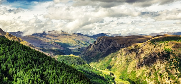 Panoramic view of beautiful valley near queenston, new zealand with high mountains and coniferous forest on the slope