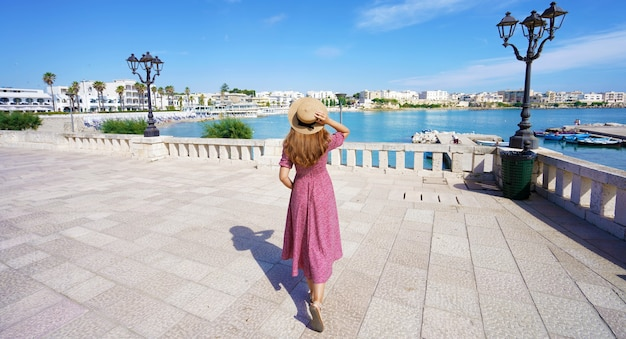 Panoramic view of beautiful young woman with hat and dress walking on promenade of otranto, apulia, italy