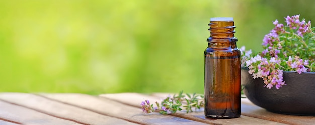 Panoramic view on a bottle of essential oil and lavender flowers in a bowl on a wooden table