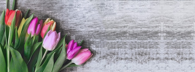 Panoramic view on a bouquet of tulips on a wooden background with copy space