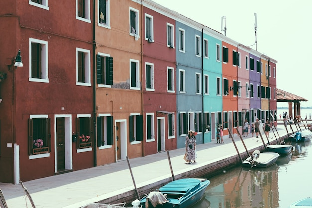 Panoramic view of brightly coloured homes and water canal with boats in burano, it is an island in the venetian lagoon. summer sunny day and blue sky