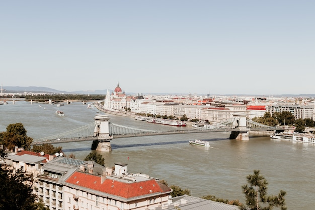 Panoramic view of the chain bridge with lions figures and panorama of the city in budapest