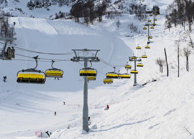 Panoramic view of chairlift at ski slopes and mountain background in rosa khutor alpine resort. sochi, russia