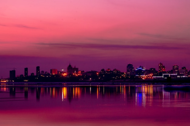 Panoramic view of city downtown during pink and purple sunset.