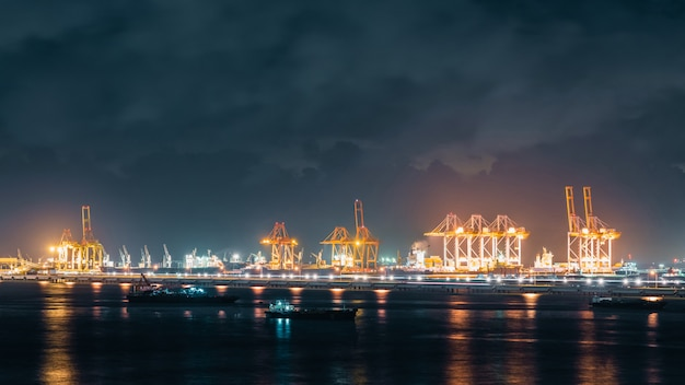 Panoramic view of cranes loading shipment containers in cargo shipping port at night